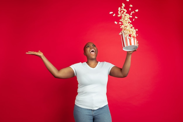 Étonné. pop-corn volant. portrait de jeune femme afro-américaine sur fond rouge. beau modèle féminin. concept d'émotions humaines, expression faciale, ventes, publicité, inclusion, diversité. espace de copie.