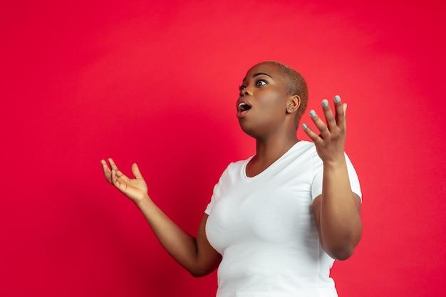 Étonné. portrait de jeune femme afro-américaine sur rouge. beau modèle féminin en chemise