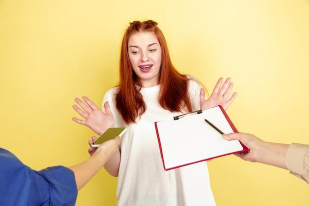 Étonné. portrait de jeune femme caucasienne sur fond de studio jaune, trop de tâches. comment bien gérer son temps. concept de travail de bureau, entreprise, finance, pigiste, autogestion, planification.