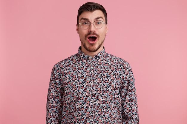 Étonné séduisant beau jeune homme portant des lunettes aux cheveux noirs non rasé avec barbe et moustache en chemise colorée a ouvert la bouche dans l'excitation, isolé