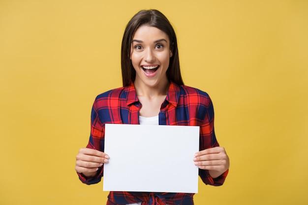 Étonnement ou femme surprise avec un panneau blanc blanc, isolé sur fond jaune.