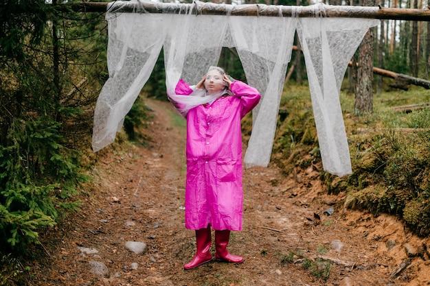 Étrange jeune femme dans un imperméable rose posant avec une étamine couvrant le visage dans la forêt