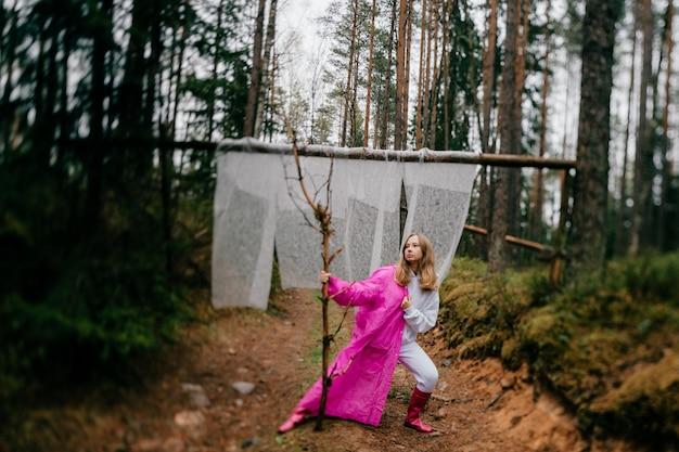 Étrange jeune femme en imperméable rose posant avec bâton dans la forêt