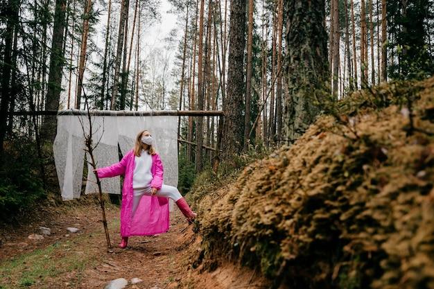 Étrange jeune femme en masque et imperméable rose posant avec bâton dans la forêt