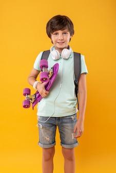 Être actif. beau garçon inspiré portant un cartable et tenant sa planche à roulettes