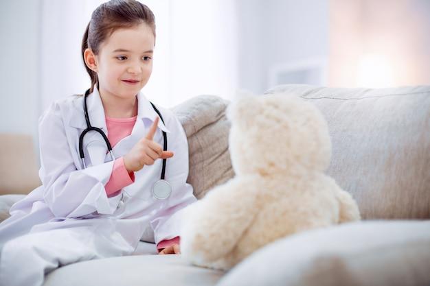 Être attentif. agréable fille occupée pensive traitant l'ours en peluche tout en portant une blouse de laboratoire et assis sur le canapé