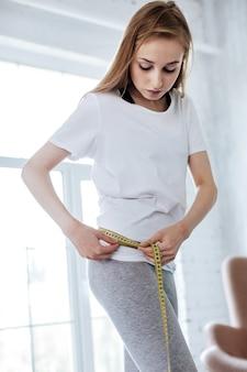 Être au régime. femme de chose sans sourire mesurant sa taille et portant des vêtements à la maison