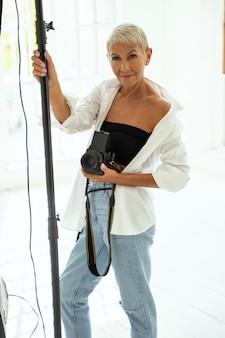 Être au travail. femme joyeuse gardant le sourire sur son visage tout en posant devant la caméra