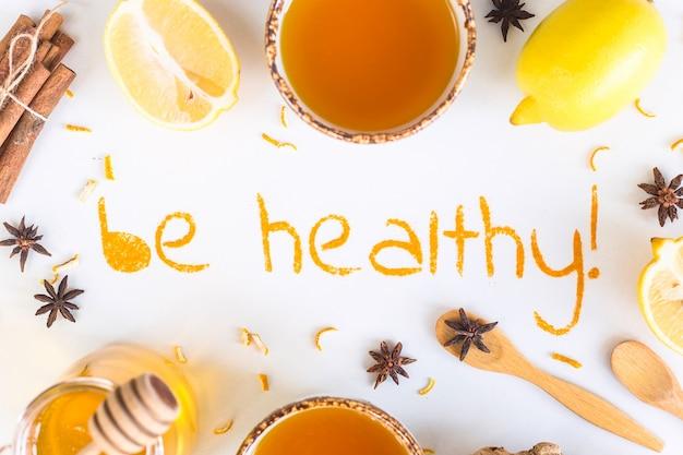 Être en bonne santé - écrit à partir de curcuma moulu sur un fond blanc