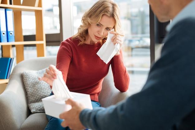 Être débordé. jeune femme triste sans joie tenant un mouchoir en papier et pleurer tout en étant dans le bureau des psychologues