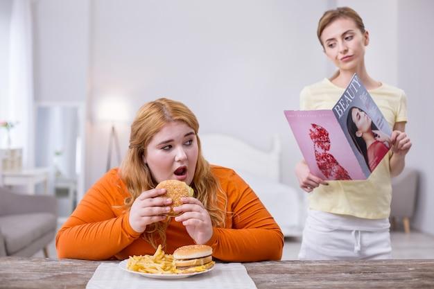 Être envieux. pauvre femme en surpoids mangeant une salade et regardant son ami mince