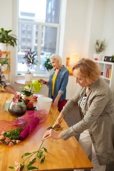 Être fleuriste. agréable femme âgée tenant une branche de fleurs tout en la coupant