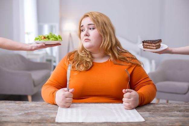 Être gros. misérable femme dodue regardant une salade et voulant des cookies