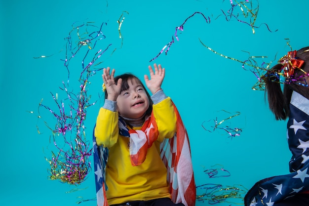 Être insouciant ensemble. heureuse petite fille trisomique jetant des rubans colorés en l'air et s'amusant