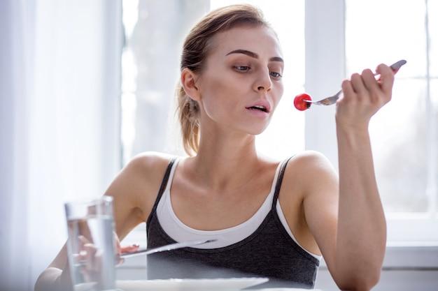 Être mince. malheureuse jeune femme mangeant une tomate tout en essayant de perdre du poids