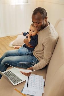Être père. homme afro-américain barbu aux yeux noirs exubérant souriant et tenant son fils sur ses genoux tout en travaillant sur l'ordinateur portable et tenant une feuille de papier
