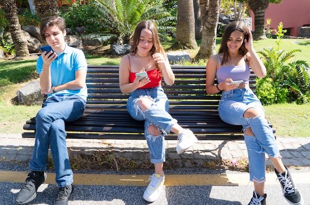 Être prudent. la distanciation sociale et le port de masques de protection du visage arbre adolescent personnes homme et femme utilisant des smartphones