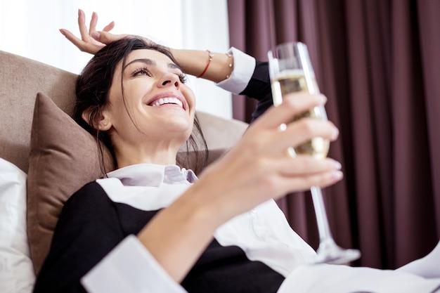 Être riche. heureuse jeune femme de chambre buvant du champagne en rêvant d'une vie meilleure