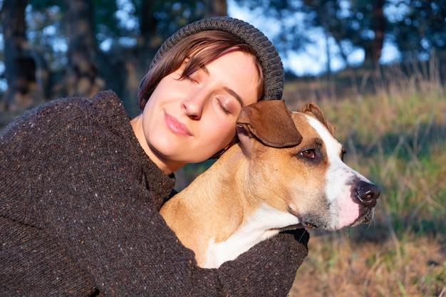 Étreindre un chien dans une nature magnifique au coucher du soleil. femme face au soleil du soir est assise avec son animal à côté d'elle