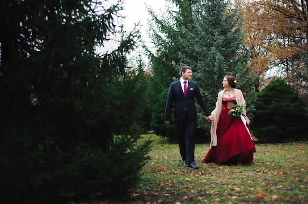 Étreinte romantique des jeunes mariés. couple se promène dans le parc