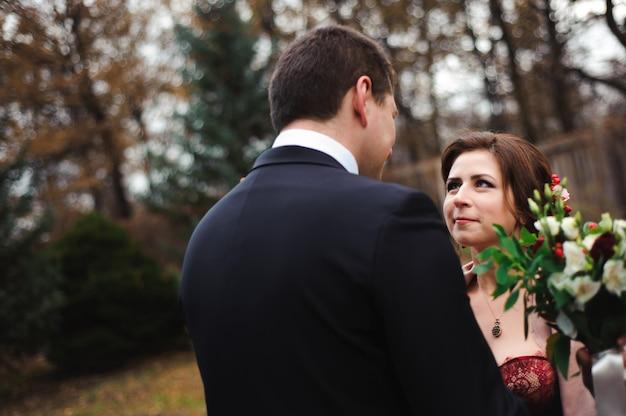 Étreinte romantique des jeunes mariés. couple se promène dans le parc.