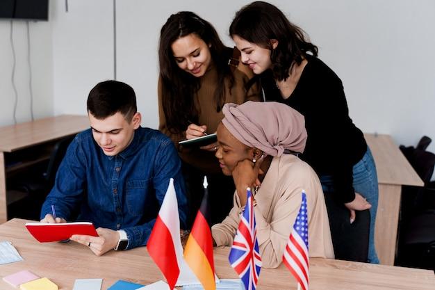 Étude de cours d'anglais avec des étudiants de différents pays: pologne, allemagne, états-unis. travail en équipe. travailler chez des étudiants multiethniques. l'enseignant étudie les langues étrangères ensemble en classe. étudier avec un ordinateur portable.