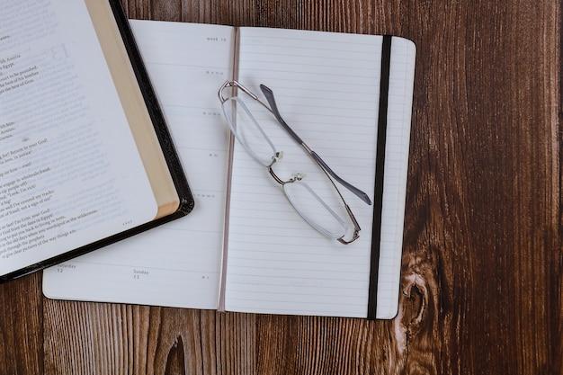 Étude du matin avec la sainte bible ouverte avec bloc-notes sur bois