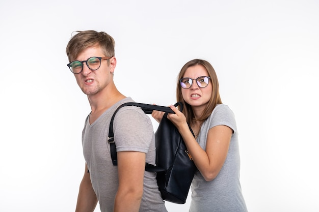 Étude, émotions, concept de gens drôles. une fille déchirant le sac du dos de l'homme.