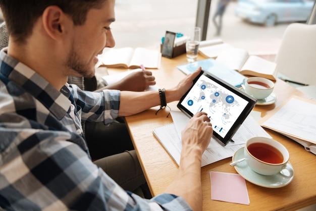 Études de commerce. jeune homme heureux lit des infographies commerciales sur tablette au café.