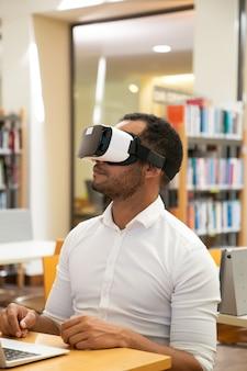 Étudiant adulte à l'aide d'un casque de réalité virtuelle