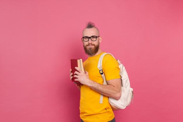 Étudiant adulte gai mec de vêtements décontractés avec barbe et sac à dos tenant des livres isolés sur rose