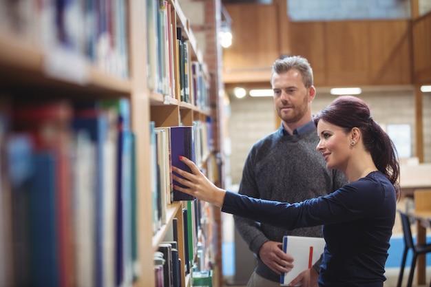 Étudiant adulte retirant le livre de l'étagère