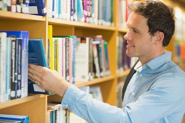 Étudiant adulte en sélectionnant le livre de l'étagère dans la bibliothèque
