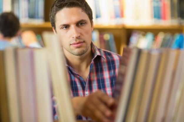 Étudiant adulte sélectionnant le livre de l'étagère dans la bibliothèque