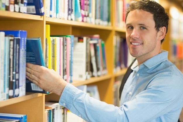 Étudiant adulte souriant, sélectionnant le livre de l'étagère dans la bibliothèque