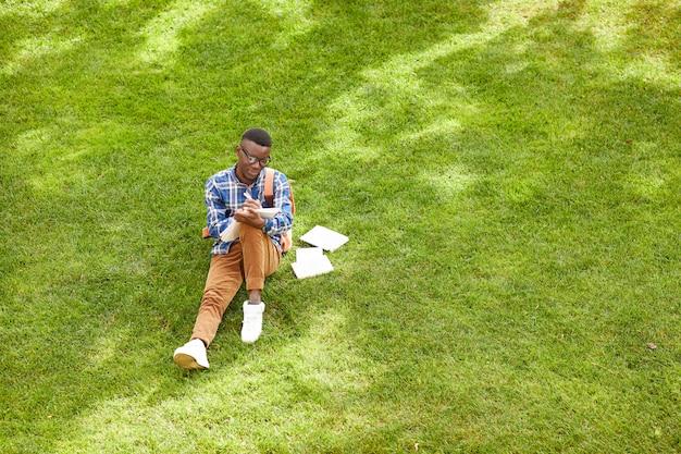 Étudiant africain assis sur l'herbe