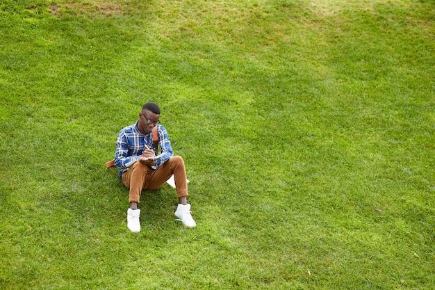 Étudiant africain assis sur la pelouse