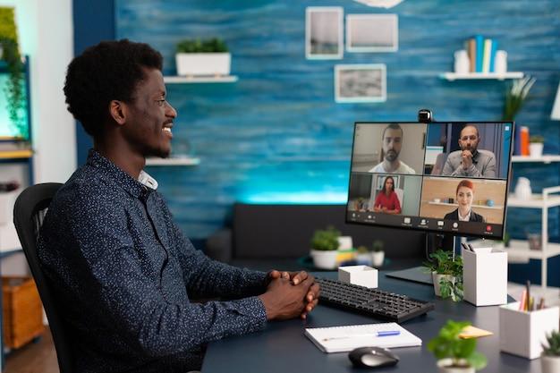 Étudiant africain ayant une conférence de réunion par vidéoconférence en ligne