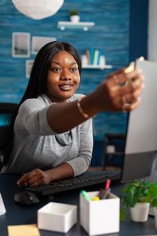 Étudiant afro-américain étudiant un cours de commerce à l'aide de la plate-forme universitaire d'apprentissage en ligne