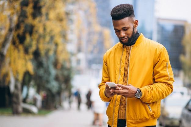 Étudiant afro-américain marchant dans la rue et parler au téléphone