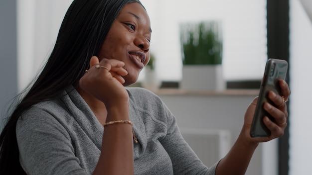 Étudiant afro-américain parlant avec un ami expliquant une leçon de mathématiques en ligne lors d'un appel vidéo numérique