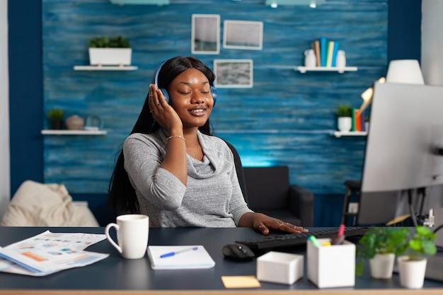 Étudiant afro-américain portant des écouteurs écoutant de la musique joyeuse assis au bureau dans le salon