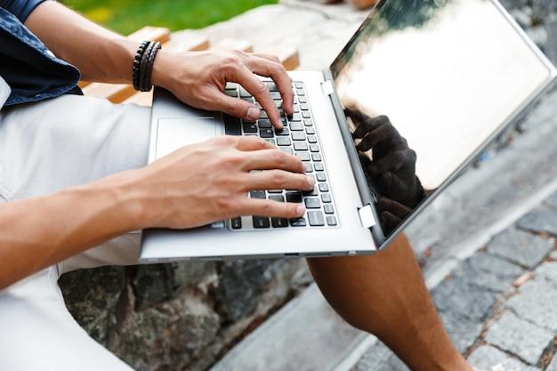 Étudiant asiatique à l'aide d'un ordinateur portable alors qu'il était assis sur un banc dans le parc