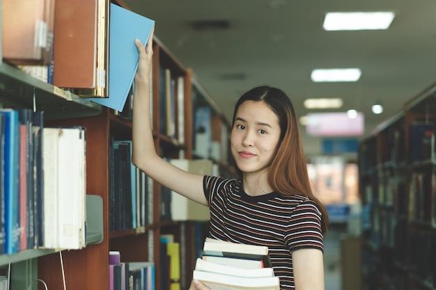 Étudiant asiatique en choisissant livre sur l'étagère de la bibliothèque.