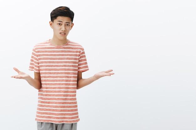 Un étudiant asiatique désemparé ne peut pas comprendre ce que le professeur veut en haussant les épaules debout avec les mains écartées sur le côté et les sourcils levés