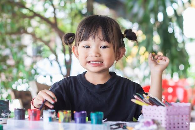 Étudiant asiatique dessinant et peignant des couleurs sur le papier dans la salle.