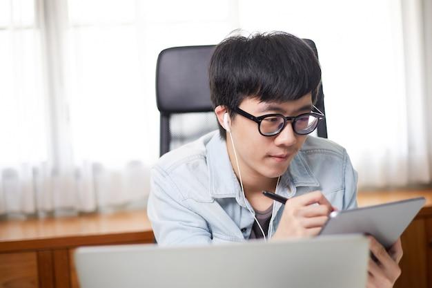 Étudiant asiatique étudiant en ligne e-learning en utilisant une tablette numérique et un ordinateur portable