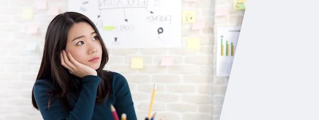 Étudiant asiatique femme pensant avec la main sur la joue