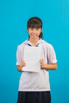 Étudiant asiatique avec fille cheveux longs tenant un cahier sur un bleu.