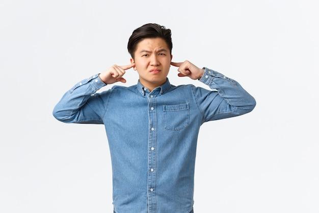 Un étudiant asiatique mécontent et dérangé se plaint d'un voisin bruyant, grimaçant mécontent, ferme les oreilles avec les doigts et semble ennuyé, dérangé par un son fort, debout sur fond blanc.